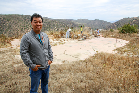 Jea Song with his sons in the background on the hilltop property where he hoped to build a home.