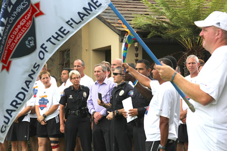 City officials greet a relay team running to bring attention to the Special Olympics World Games.