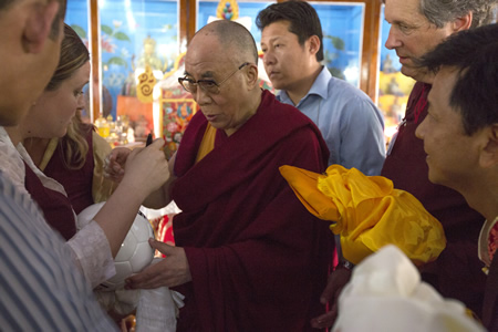 The Dalai Lama visits an India refugee settlement for Tibetans that locals Tom Lamb and Tenpa Dorjee, right, support.