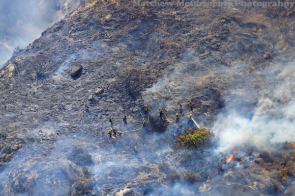 Firefighters encircle a blaze in Laguna Canyon. Photo by Mike McClements