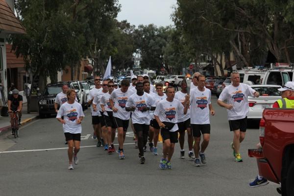 Special Olympics Final Leg torch bearers run through downtown Laguna Beach on Monday.