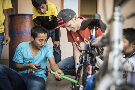 In Antigua at the Education For The Children school, Tom Oehler shows a recipient of a new bike basic maintenance. Photos by Stefan Voitl.