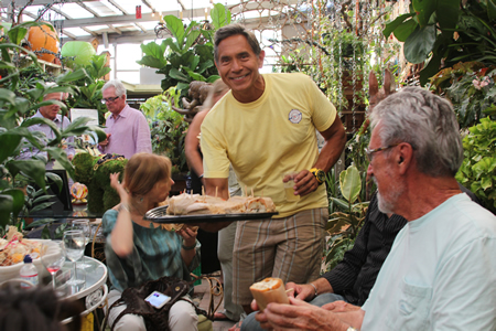 Ever the host, landscape contractor Ruben Flores offers friends and customers refreshment during a hectic store closing party last week .Photo by Andrea Adelson