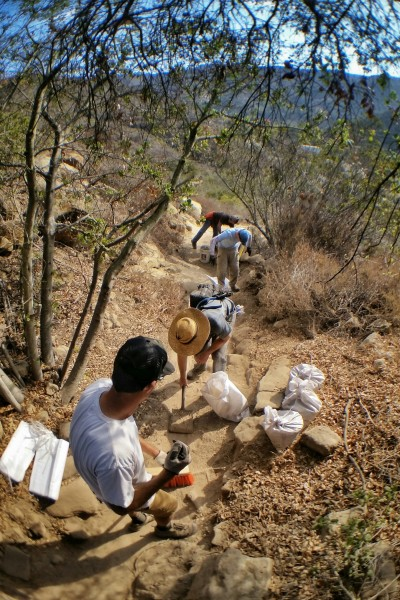 "Caption: Canyon Foundation staff Mike Hall and Alan Kaufmann work with volunteers removing ""cake mix"" dust kicked up by mountain bikers from Laguna Ridge Trail near Big Bend. The dirt will be used to rebuild trails when it rains. Photo by Bill Freeman."