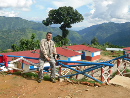 "Rabin Situala overlooks the ""new"" Pahari village, on a remote mountain ridge top in rural Nepal where R Star had gifted the village's women goats. Thanks to Situala's advocacy, the village has 20 permanent, earthquake resistant homes, with plans for more."