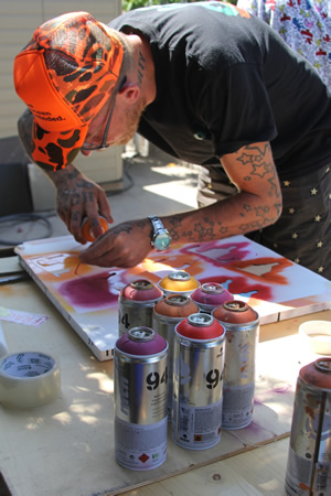 The street artist working on small canvases for a gallery show.