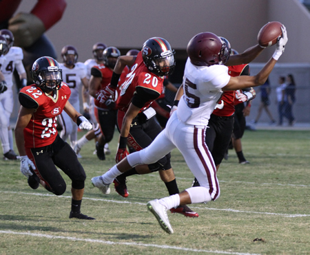 : Sophomore Adam Armstrong and an unidentified teammate coral Segerstrom running back JC Caravez during Laguna's 45-0 road loss on Friday, Sept. 11. Credit: Dante Fornaro