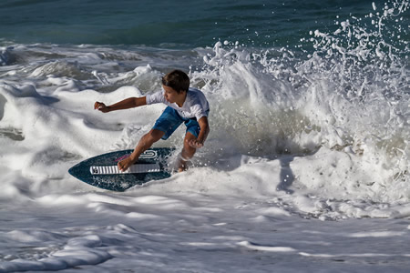 Nine year-old James Paracuellos from Laguna Beach cuts a rooster tail of foam through an early morning wave