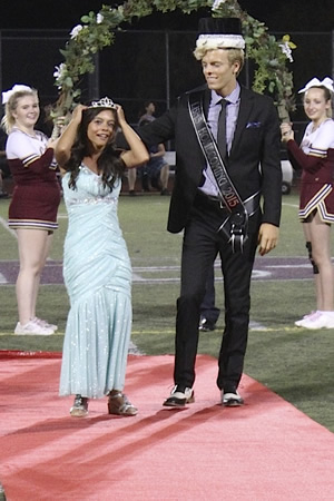 Queen Moe Howson escorted by homecoming king Penn Nielsen.