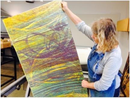 Laguna Beach artist Sheryl Seltzer holds up a work in progress.