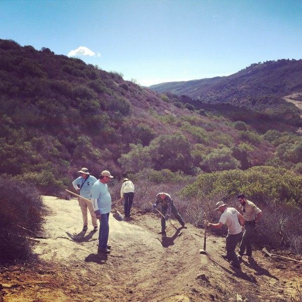 Building an erosion-abetting berm, from left, David Heuer, Rodney Ferguson, Tom Taylor, Mike Hall, Ranger Zach Salazar and Alan Kaufmann bolster the trail at Five Oaks in Aliso-Wood Canyons.