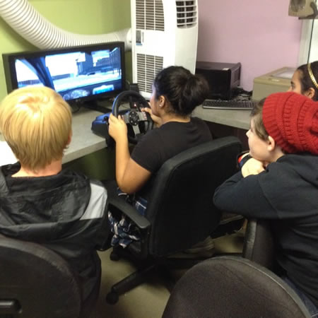 Teens try out the UPS driving simulator.