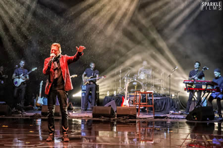 Kenny Loggins steps into the rain from under a sheltering stage during a December concert in the Irvine Bowl. Photo by Sparkle Films.