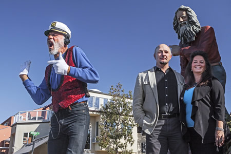 Martin and Tabitha Yewchuk, right, are making a film about Laguna Beach's greeters past and present. Michael Minutoli, left, takes up a role inhabited by Eiler Larsen, depicted in a sculpture at Brooks Street and Coast Highway. Photo by Mitch Ridder.