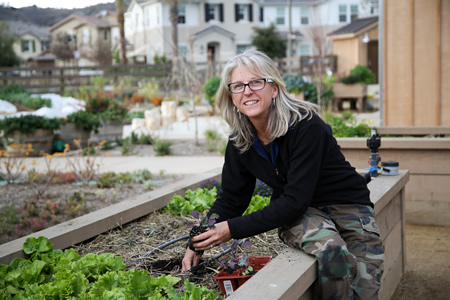 """Laguna Beach resident Gloria Broming ditched a corporate job to become a """"community farmer,"""" seen here working in a San Juan Capistrano garden.Photo by Jody Tiongco."""