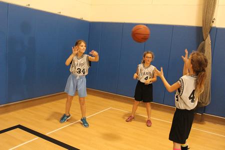 :Girls learn hoop skills before games start.