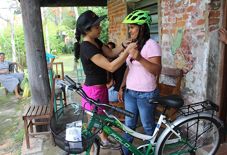 Belen Ramirez, left, offers safety advice to a Puerto Casado resident who received a bike courtesy of Bike Project Love. Photo taken by Erin Machan.