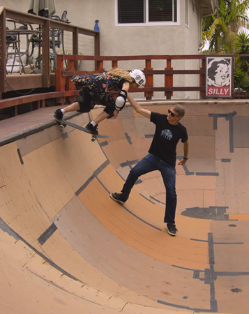 Barbara Odanaka receives technique tips from skateboard pro and skate park promoter Tony Hawk in Encinitas last year. Photo by Howard Dvosky.