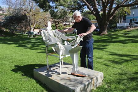 """Artist Leonard Glasser inspects one of the two """"Sunbathers"""" sculptures prior to a hearing this week over whether they should be restored again. Photo by Jody Tiongco."""