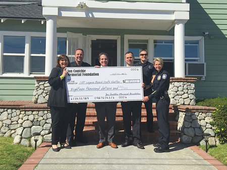 Police Chief Laura Farinella, right, and other officers in the department present a check to shelter supporters.