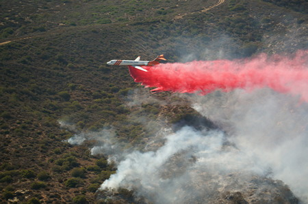A retardant-dropping plane douses a wildfire in Laguna Canyon set off by sparks from a power line last summer. Photo by Greg Farnes