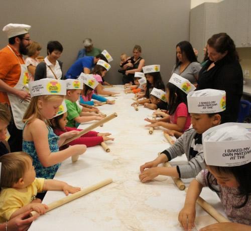 Kids roll dough for holiday matzah.