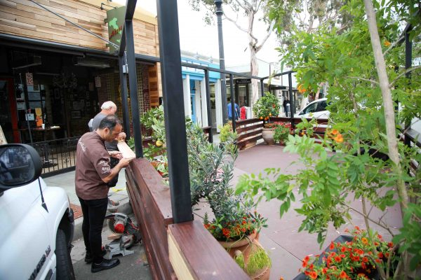 In May, Chef Alessandro consults with the parklet builder over its progress.