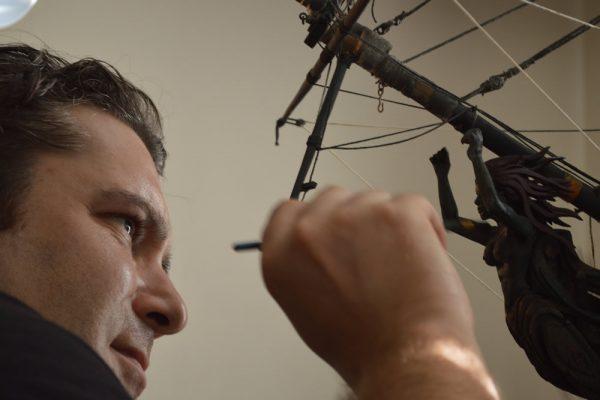1)Jordan Dimitrov works on a model sailing ship.