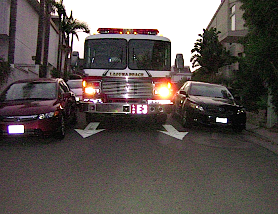 A fire engine maneuvers through a narrow street where parking is allowed on either side.Photo courtesy of city committee report.