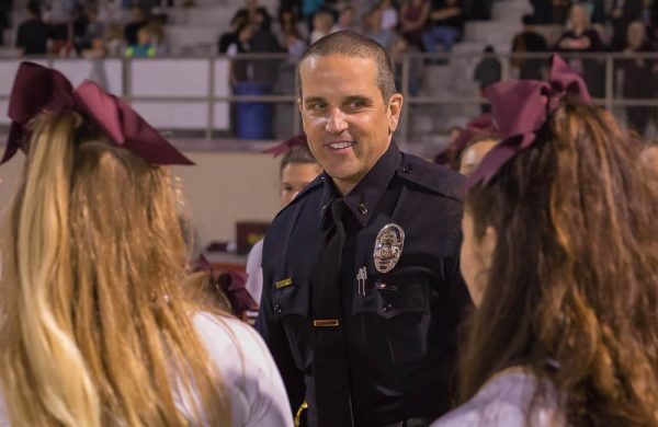 Laguna Beach Police Lieutenant, Jeff Calvert, hands out snap on bracelets to Laguna's Cheer squad.