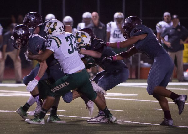 Bruce Knill drags defenders ahead for a four yard run in the first quarter. Knill gained 79 yards on 11 carries.