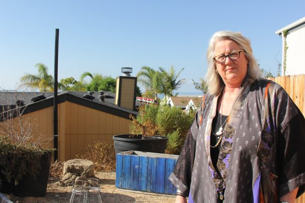 Michele McCormick outside the pipe that vents sewer gases from her home in Laguna Terrace Park.
