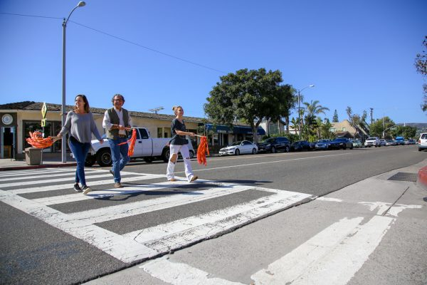 Laguna Exchange owner Don Sciortino, center, and his employees use flags he devised for buckets affixed to posts at the intersection of Anita Street and Coast Highway to assist pedestrians cross  .