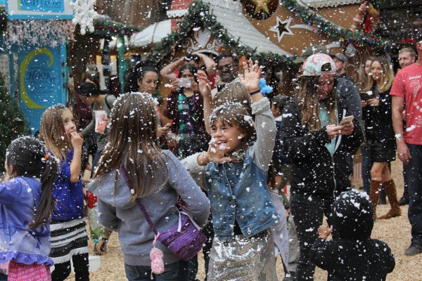 Visitors delight in faux snow that fills the Sawdust Winter Festival town square.