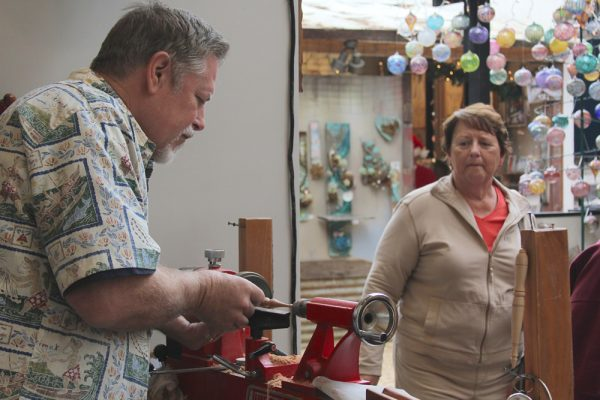 David Morgan shapes wood into beer steins, ornaments and even headgear while in his Sawdust Festival booth.