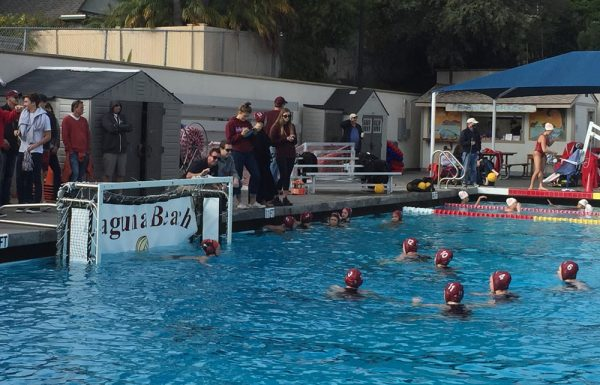 Coach Ethan Damato gives guidance to the Breakers during a timeout in the contest this past Saturday, Jan. 21, against Mater Dei. Breakers went on to defeat the Monarchs 11-6, their third win over the second-best school. In the pool: # 1 Thea Walsh, # 3 Alana Evans, # 12 Aria Fischer, # 10 Alex Peros, # 11 Evan Tingler, # 4 Isabel Riches, # 6 Claire Sonne.