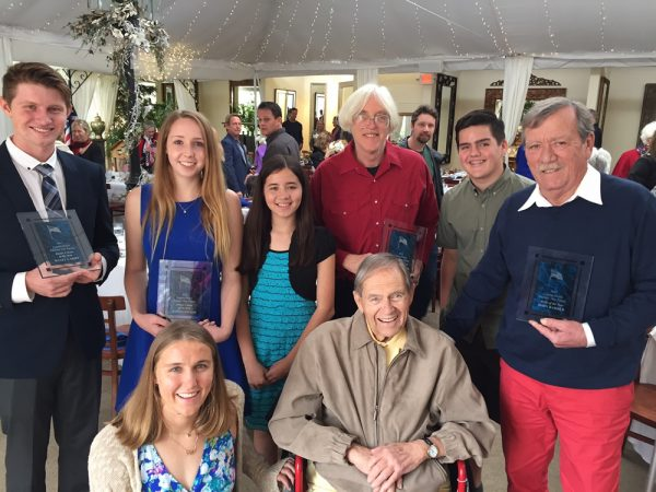 From left, seated: Grand marshal Aria Fischer and honored patriot Major Robert W. Sternfels, USAAF. Standing, from left, junior citizens Wyatt Shipp and Madison Sinclair, essay winner Claire Tigner, citizen of year Douglas Miller, program cover artist Jared Ghetian, and artist of the year John Barber.