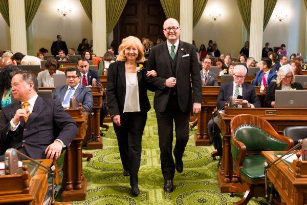 Sande St. John receives an escort from Assemblyman Matthew Harper.