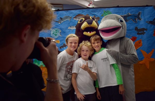 Fifth-graders, from left, Nick Rogers, Jude Young and Peter Coccas alongside Pacific Marine Mammal Center mascot Sammy the sea lion and TOW school mascot Topper the dolphin during a student club's Ocean Awareness Night.