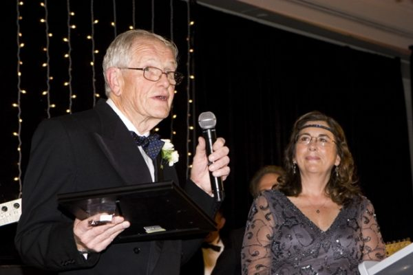 Friendship Shelter founder Colin Henderson accepts an award from Dawn Price, the organization's executive director.