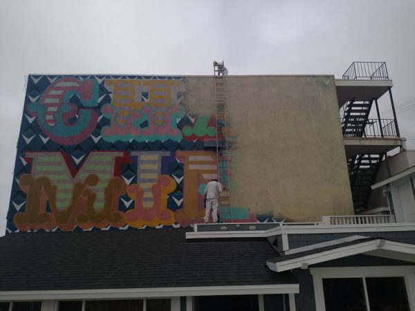 "Painters last week cover up the short-lived ""Charming"" mural, installed clandestinely by British street artist Ben Eine in 2015. Photo by Brad Wood."