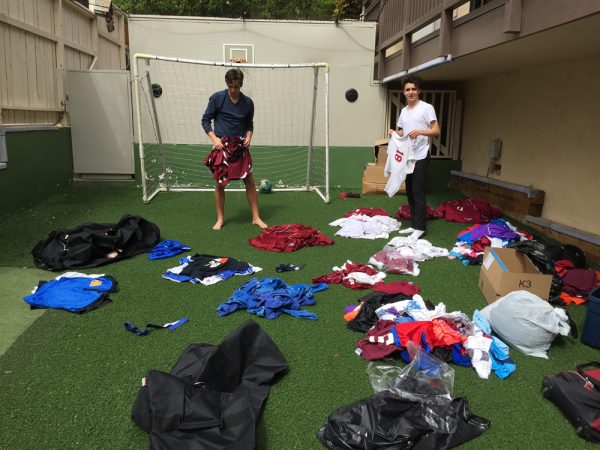 Sterling Butler and James Langton sort through the latest donation of uniforms in backyard of one of their homes.