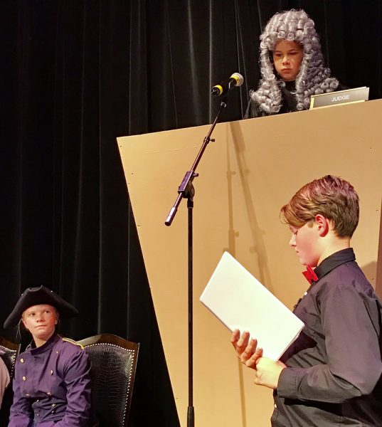 Defense attorney Keegan Thomas, right, questions witness Tess Genske as the judge, played by Presley Cortez, oversees the trial of the pirate Blackbeard, the culmination of a Thurston Middle School forensics class Friday, June 3.