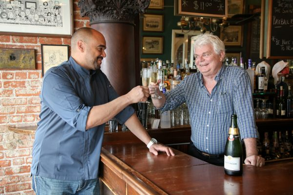 Chef Norm Theard and Saloon owner Michael Byrne offer a hopeful toast to a new venture Roux, a Creole inspired restaurant they expect to open soon where Café Zoolu operated. Photo by Jody Tiongco.