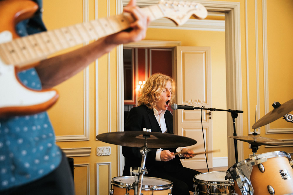 Jake plays the drums with passion during the filming of a music video. Photo by Sam Dameshek.