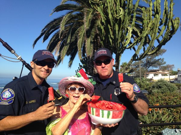 Firefighters take a break from flapjack flipping to sample watermelon pops provided by local Jessica DeStefano.