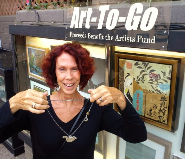 : Festival of Arts jewelry artist Kate Cohen displays her donation to Art-to-Go benefit.