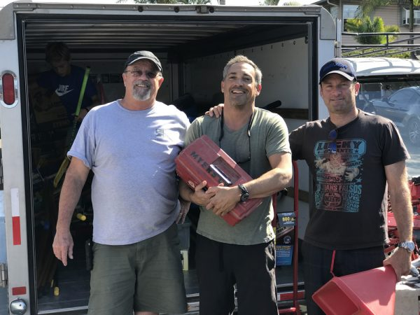 Josh Nuefeld, center, with the nail gun donated by Sonny Myers, left, and John Cressy, right. Photo by charlie Craig.