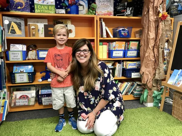 Caleb Cornell visits the reading corner and gets a hug from his new kindergarten teacher, Mary Blanton.