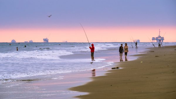 A shore fisherman tries his luck in August in Newport Beach, where pre-moratorium oil platforms off Huntington Beach fill the horizon.Photo by Ian D. Keating